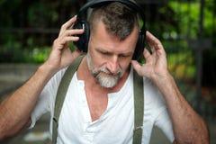 Homem farpado considerável em seu 50s com fones de ouvido Imagens de Stock Royalty Free
