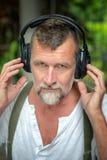 Homem farpado considerável em seu 50s com fones de ouvido Foto de Stock Royalty Free