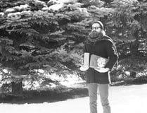 Homem farpado considerável, moderno, com barba e bigode em óculos de sol, no chapéu, no revestimento e no lenço pretos com caixas fotografia de stock royalty free