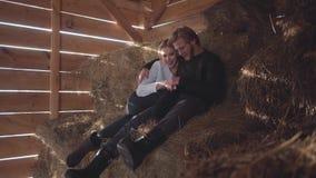 Homem farpado considerável nos vidros e na mulher bonita sem pano morno que senta-se no feno no celeiro frio do inverno novo video estoque