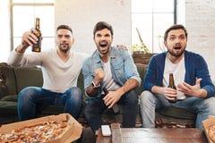 Homem farpado considerável que aumenta uma garrafa da cerveja fotos de stock