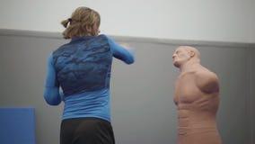 Homem farpado considerável que golpeia o manequim com sua palma no gym Pugilista seguro novo que bate o manequim do corpo humano filme
