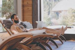 Homem farpado considerável que usa o laptop ao descansar no hotel dos termas Homem que relaxa após o dia difícil no salão de bele imagens de stock