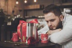 Homem farpado da forma que espera uma menina em um café imagens de stock royalty free