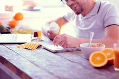 Homem farpado de irradiação que faz algumas anotações ao conduzir dieta equilibrada fotos de stock royalty free