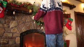 Homem farpado de sorriso na grinalda de suspensão kniited do Natal da camiseta acima da chaminé decorada com a festão de piscamen vídeos de arquivo