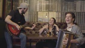 Homem farpado de sorriso novo que joga a guitarra na barra, seu amigo que joga o acordeão quando assento gordo atrativo da mulher filme