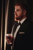 Homem farpado do gengibre novo que mantém um vintage de vidro com vinho tinto contra a luz, preta no fundo Perfil da vista Fotos de Stock Royalty Free