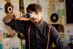 Homem farpado do moderno à moda que guarda a câmera velha do filme Foto de Stock Royalty Free