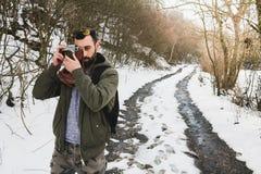 Homem farpado do moderno com a câmera retro que está nas montanhas dianteiras foto de stock