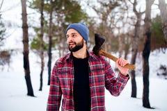 Homem farpado do moderno em uma floresta nevado do inverno com machado em um ombro Posição do lenhador na inspeção do homem da fl fotografia de stock