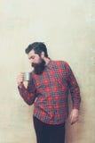 Homem farpado do olhar severo com a barba que guarda a caneca do metal fotos de stock royalty free