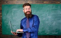 Homem farpado do professor com fundo moderno do quadro do portátil Instrução em linha Educação da tecnologia de Digitas moderno fotos de stock