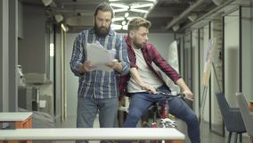 Homem farpado do retrato que estuda papéis no escritório Colega novo que monta a bicicleta no escritório e no indivíduo farpado d vídeos de arquivo