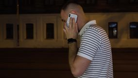 Homem farpado em camisa branca e preta listrada de t que anda na rua na noite e na conversa pelo telefone celular ou pelo telefon filme