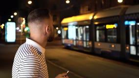 Homem farpado em iqos eletrônicos do cigarro do fumo listrado da camisa do polo t na noite na rua com os carros no fundo vídeos de arquivo