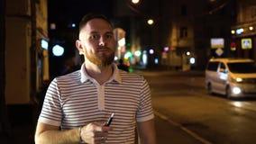Homem farpado em iqos eletrônicos do cigarro do fumo listrado do polo na noite na rua com os carros no fundo e no passeio para ba video estoque