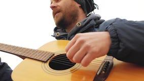 Homem farpado em um chapéu feito malha que joga uma guitarra e que canta vídeos de arquivo