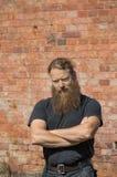 Homem farpado em um fundo da parede de tijolo vermelho imagem de stock