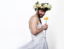 Homem farpado em um vestido de casamento do ` s da mulher em seu corpo despido, guardando uma flor Em sua cabeça uma grinalda das Imagens de Stock