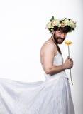 Homem farpado em um vestido de casamento do ` s da mulher em seu corpo despido, guardando uma flor Em sua cabeça uma grinalda das Fotos de Stock Royalty Free