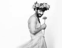 Homem farpado em um vestido de casamento do ` s da mulher em seu corpo despido, guardando uma flor Em sua cabeça uma grinalda das Imagem de Stock