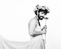 Homem farpado em um vestido de casamento do ` s da mulher em seu corpo despido, guardando uma flor Em sua cabeça uma grinalda das Imagens de Stock Royalty Free