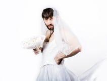 Homem farpado em um vestido de casamento do ` s da mulher em seu corpo despido, guardando uma flor Em sua cabeça uma grinalda das Imagem de Stock Royalty Free