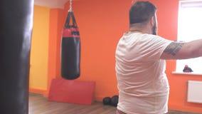 Homem farpado gordo cansado do encaixotamento do treinamento um saco de perfuração no gym, esporte vídeos de arquivo