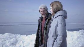 Homem farpado louro bonito que anda com a mulher bonita que guarda as mãos Opinião de surpresa um polo norte ou sul nevado no vídeos de arquivo