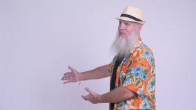 Homem farpado maduro feliz do turista que mostra algo video estoque