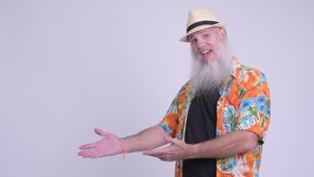 Homem farpado maduro feliz do turista que sorri e que mostra algo video estoque