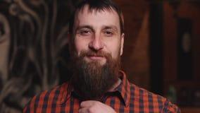Homem farpado maduro novo que afaga seus barba e sorriso filme