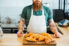 Homem farpado no avental que está e que guarda tenazes de brasa para croissant Fotografia de Stock