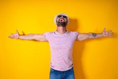 Homem farpado no chapéu e nos óculos de sol que levantam com mãos acima Foto de Stock Royalty Free