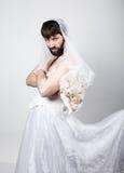 Homem farpado no vestido de casamento de uma mulher em seu corpo despido, guardando uma flor em sua cabeça um véu noiva farpada e Imagem de Stock