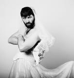 Homem farpado no vestido de casamento de uma mulher em seu corpo despido, guardando uma flor noiva farpada engraçada, preto e bra Fotografia de Stock
