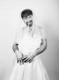 Homem farpado no vestido de casamento de uma mulher em seu corpo despido, levantando noiva farpada engraçada, preto e branco Fotos de Stock Royalty Free