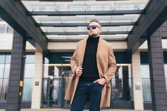 Homem farpado novo com penteado moderno e posição na moda do revestimento perto do centro de negócios foto de stock royalty free