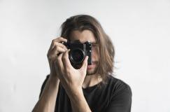 Homem farpado novo considerável com um cabelo longo e em uma camisa preta que guarda a câmera antiquado do filme do vintage em um fotos de stock royalty free