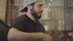 Homem farpado novo da habilidade que joga a guitarra na barra que olha a câmera Lazer no bar da cerveja video estoque