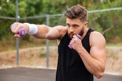 Homem farpado novo dos esportes que faz o exercício com pesos pequenos Imagens de Stock Royalty Free