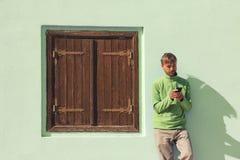 Homem farpado novo em suportes verdes da camisa perto da parede com uma janela e um smartphone de madeira velhos dos usos Conceit imagem de stock