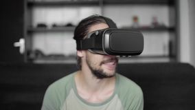 Homem farpado novo feliz do moderno que usa sua exposição dos auriculares de VR para o jogo da realidade virtual ou olhando o víd