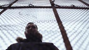 Homem farpado novo no Parka do inverno atrás da cerca do elo de corrente video estoque