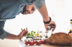 Homem farpado novo que cozinha o jantar em casa fotos de stock royalty free