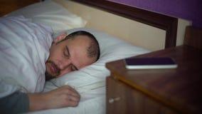 Homem farpado novo que dorme na cama video estoque