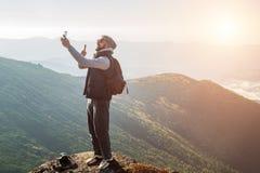 Homem farpado novo que faz o selfie nas montanhas no alvorecer imagens de stock