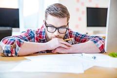 Homem farpado pensativo no funcionamento de vidros com blueprits Imagem de Stock Royalty Free