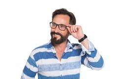 Homem farpado positivo carismático que olha afastado através dos vidros fotografia de stock royalty free